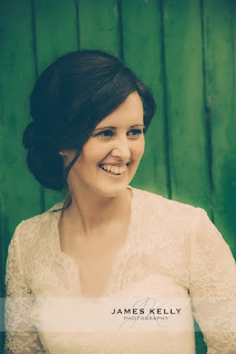 Girl smiling in front of a green door wearing a vintage lace wedding dress with finger waves in her hair