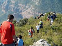Baixant pels espadats del Serrat de l'Onyó amb els conglomerats vermells de la Roca Rodona i la Roca del Migdia com a fons