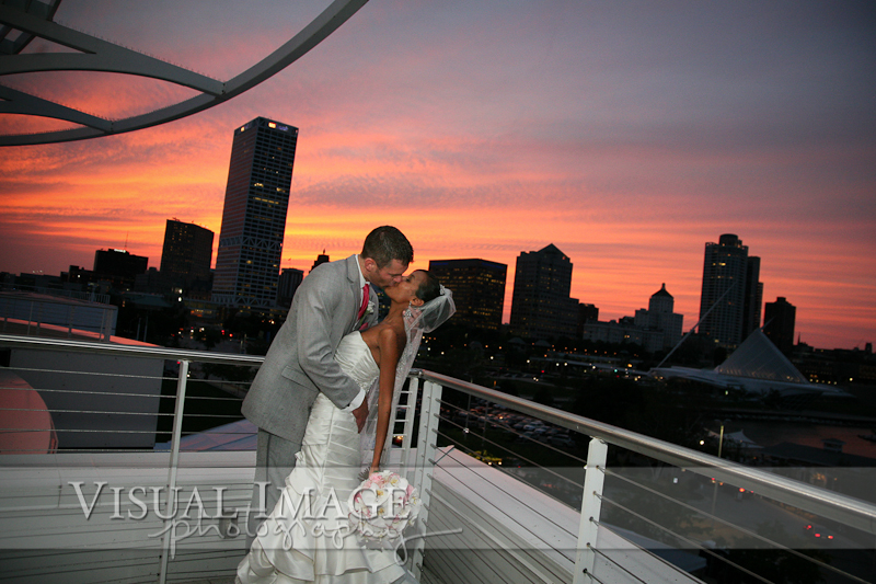Bride and groom kissing outside the Pilot House with beautiful orange sunset over Milwaukee skyline