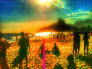 Pessoas aguardando o pôr do sol em ipanema.
