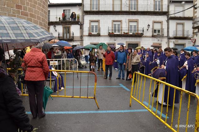 Personas esperando bajo la lluvia a la procesion del domingo de ramos