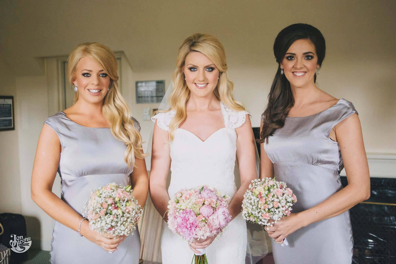 Bride and bridesmaids holding simple wedding bouquets with soft wavy hair and flawless makeup