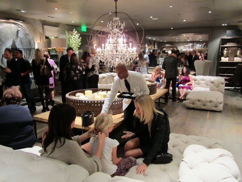 People mingling at the new Restoration hardware on white fully tufted sofas and sectionals