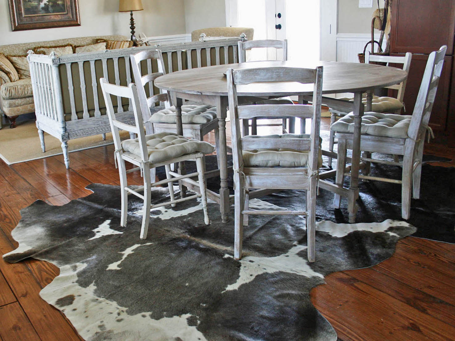 skinny on decorating with cowhide rugs rugs under kitchen table On a sad note it did not occur to me beforehand that the black rug would make every hair shed by our collie as obvious as dandruff on a dark suit
