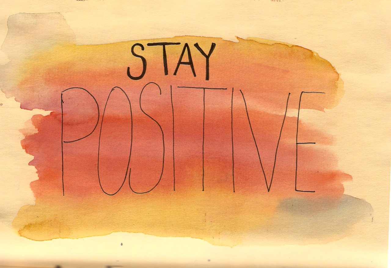Orange watercolor background with stay positive written on top