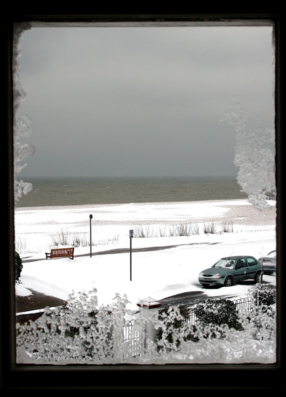 deserted snowy beach seen through a frosty window