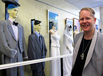Man in a tail coat standing next to a line of mannequins in wedding outfits.