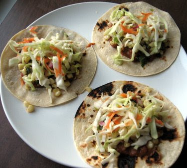 tacos with refried beans, corn with green onion, and curtido de repollo