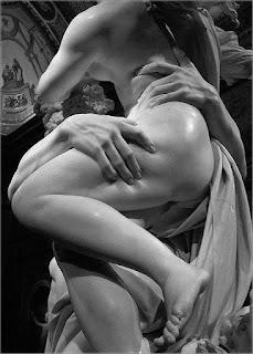 Foto em preto e branco de parte de uma escultura em mármore: O rapto de Proserpina. O deus Hades sustenta a deusa Proserpina na altura dos ombros, nua, com o corpo em perfil ; a perna esquerda pousa levemente sobre a outra e produz sombra no joelho direito; o delicado pé esquerdo, voltado para baixo está no ar. A mão direita de Hades segura fortemente a coxa de Proserpina, os dedos pressionam a carne de aspecto firme; a outra mão de Hades enlaça vigorosamente a cintura da deusa, o dedo indicador afunda na carne lateral das costas e forma um L com o dedo polegar. No topo, parte das pontas dos cabelos cacheados de Proserpina ao vento, nas costas, uma sombra contrasta o brilho de um foco de luz sobre o ombro e, parte do braço em angulo, revela uma porção do pequeno seio esquerdo próximo aos cabelos ondulados de Hades; a mão da deusa se lança a frente do corpo e atinge a cabeça de Hades. Entre os corpos vigorosos, um manto ondula em pregas. No teto, uma pintura com duas figuras humanas.