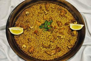 Paella de arroz y conejo con caracoles