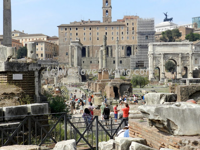 Tours are walking among the ruins of the Forum in Rome, Italy