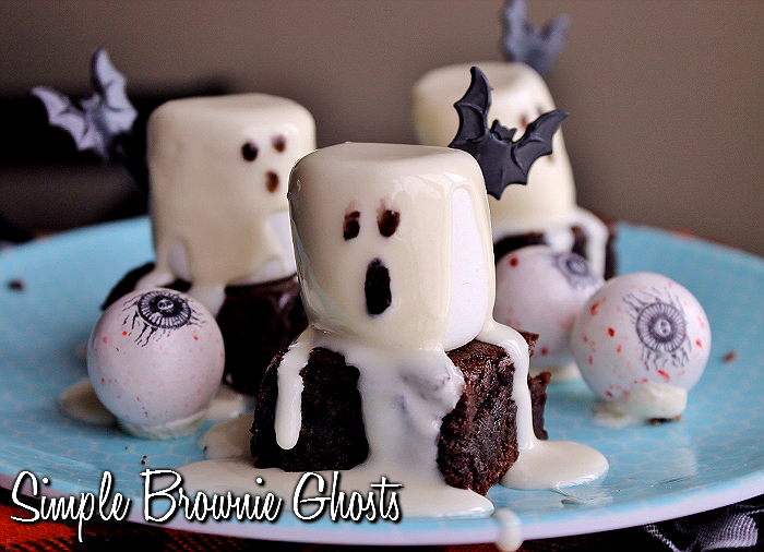 "Simple Brownie Ghosts- Simple Directions: Start with brownies- I do not care how you get brownies, I won't tell if you slaved over them for hours or not. Cut them into squares about 2"" in width. Place 1 Jumbo Marshmallow atop each brownie square. Place the pre-made frosting of your choice into a microwave safe bowl and heat on high at 5 second increments until it can be stirred into an even liquid format. Spoon melted frosting over your mallows, allowing it to drip down the side like flowy ghost 'sheets.' Squirt some black food color or decorating gel on a plate and daub the end of a chopstick/skewer/cake pop rod (etc) into the black and daub tiny faces on your ghosts. Refrigerate until serving and enjoy!"