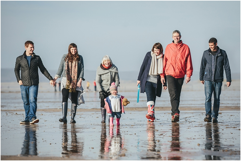 An extended family walking across the beach at Westward Ho!