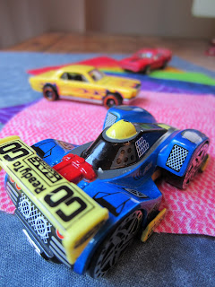 close up of matchbox F1 car on coloured fabric swatches. two other cars in the background.