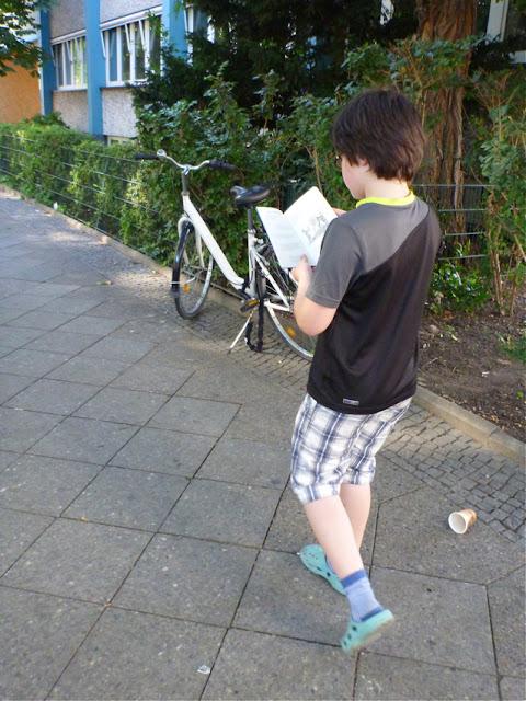 Ein kleiner Junge liest im Gehen ein bebildertes Taschenbuch, er trägt kurze Hosen und Plastiklatschen, die von einer ähnlichen hellblauen Farbe sind wie vertikale Pfeiler einer Fassade im Hintergrund
