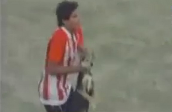 Bella Vista player Enzo Jimenez is seen grabbing a pitch invading dog by its neck