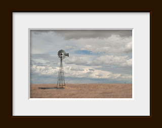 A western prairie photo of a windmill on the high plains of Colorado surrounded by grasslands. Pawnee National Grassland, Colorado