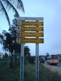 Road sign listing distances to prominent tourist attractions on Mysore Road