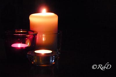 Ett tänd blockljus omgivet av tända värmeljus. foto: Reb Dutius