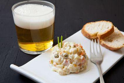 Aardappelsalade van gele aardappels in de schil geserveerd met vinaigrette en bieslook