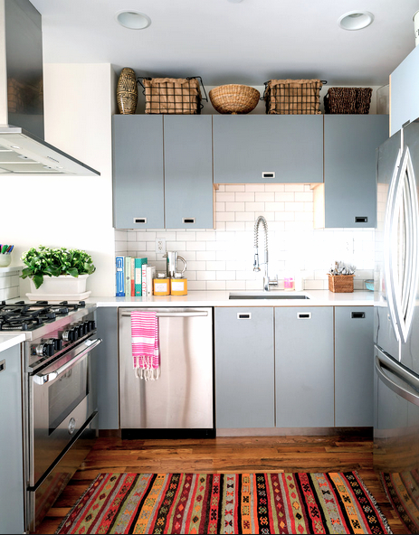 Kitchen in Anne Maxwell's colorful NYC loft apartment with powder blue flat doors, Caesarestone counters, and a Peruvian rug