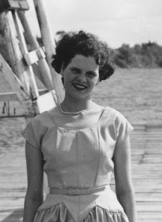 Black and white photo of a young woman on a dock.