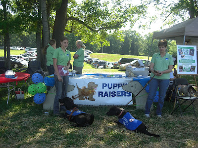 Picture of Rudy, Lexie (another guide dog puppy), I & Lexie's puppy raiser in front of our SEGDI booth