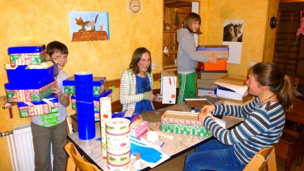 Familie Taege beklebt Schuhkartons für Weihnachten im Schuhkarton