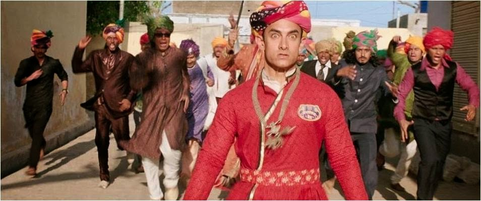 People running behind PK Aamir Khan who is in pagdi (turban) and Rajasthani dress