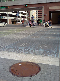 Crosswalk in downtown Indianapolis with blue painted lane with wheelchair user symbol. To the left is a walking lane & a bike lane to the convention center