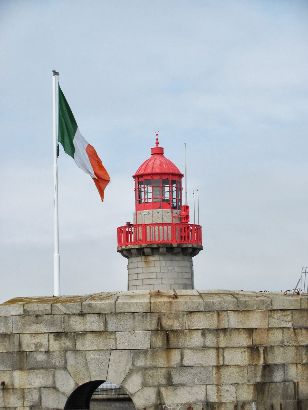 The lighthouse and the Irish National Flag on the pier at Dun Laoghaire, Co. Dublin, Ireland
