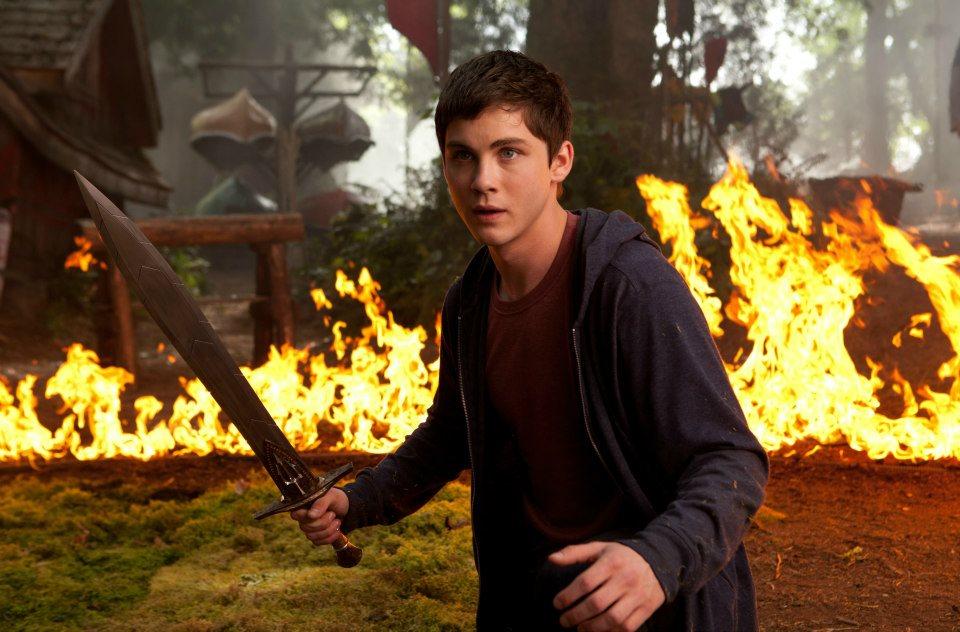Logan Lerman caracterizado de Percy Jackson en una imagen oficial de la película El Mar de los Monstruos. Vemos a Percy con Riptide en alto y con una barrera de fuego detrás.