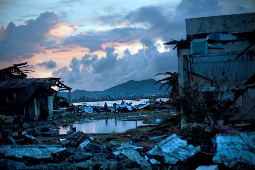 Typhoon Haiyan survivors walk through the ruins of their neighborhood on the outskirts of Tacloban, central Philippines on Nov. 13. (David Guttenfelder/Associated Press) #