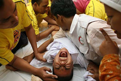 Boy screaming in pain during forced circumcision.