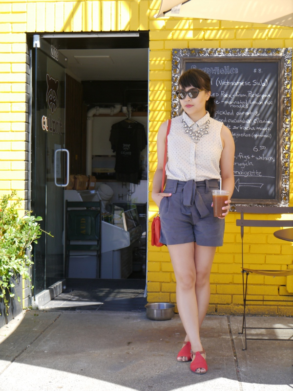 Vancouver fashion blogger Lisa Wong stands in front of a local coffee shop wearing a JACHS sleeveless blouse, Cici tie-waist shorts from Two of Hearts Boutique, a sparkly J. Crew statement necklace, Ray Ban cat-eye shades, a Roots bag, and Rachel Comey x Urban Outfitters sandals.