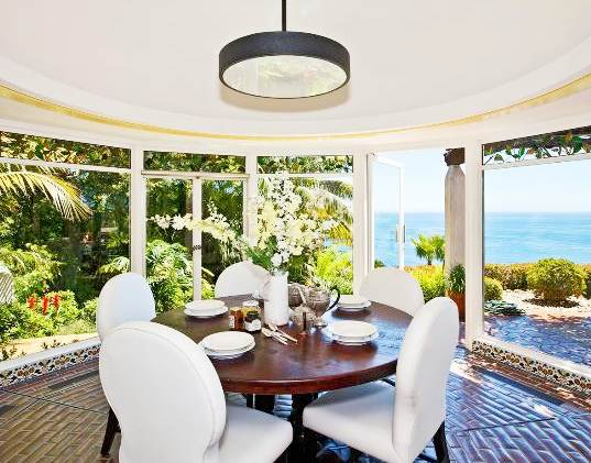 breakfast nook with tile floor, round wood table surrounded by white upholstered chairs and glass walls showing off the beautiful ocean and garden views