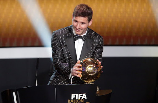 Barcelona forward Lionel Messi receives the FIFA Ballon d'Or 2012 trophy