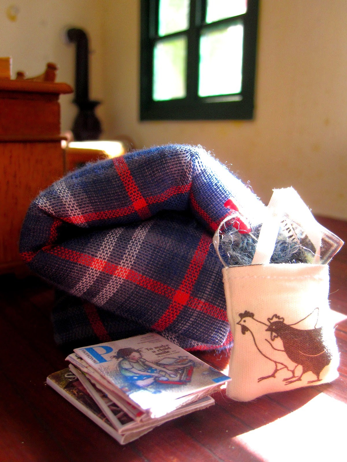 Inside of a miniature holiday house, showing a doona rolled up on the floor next to a pile of magazines and a bag of knitting.