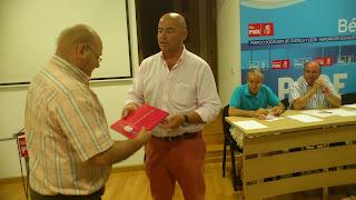 El secretario general, Javier Garrido, entrega el libro de la agrupación a un nuevo militante