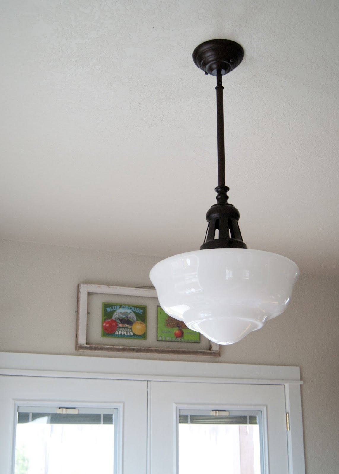 large schoolhouse light with oil bronze finish and milk glass shade