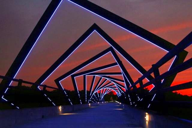 This bridge is part of a rail trail in Iowa. The decorative structure on top was inspired by the view down a mineshaft, in honor of the miners who worked in the area.