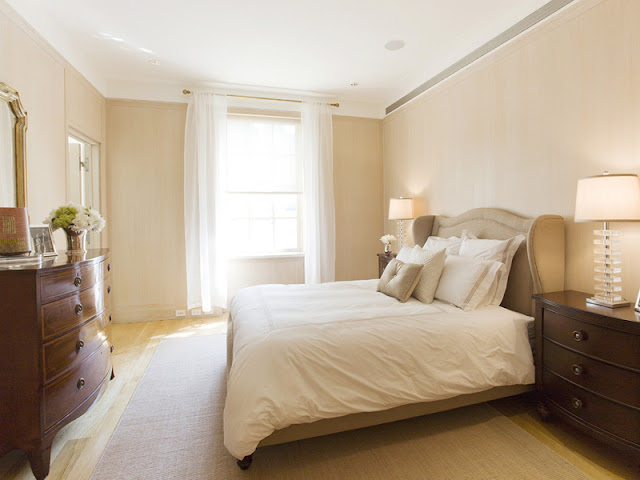 guest bedroom in an upper east side apartment with a molded headboard, white floor length curtains and a wooden chest of drawers