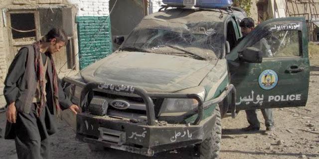Petugas keamanan memeriksa sebuah mobil polisi yang hancur akibat serangan bom bunuh diri di Kandahar