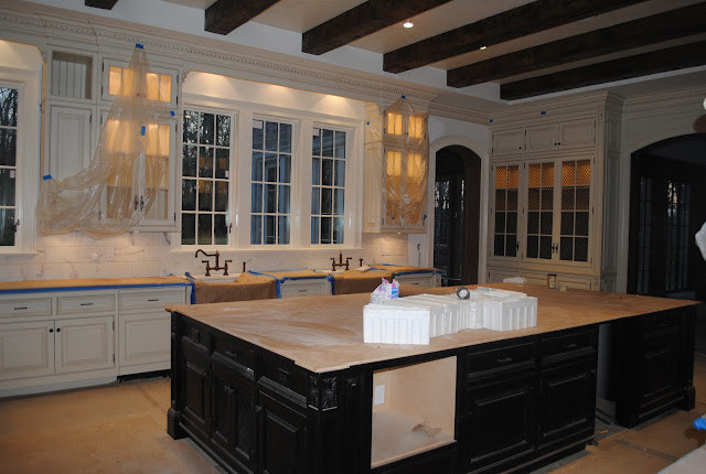 during construction of Enchanted Home Tina's French Country kitchen with white cabinets, wood beams, and black island