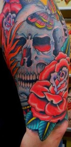 Half sleeve tattoo of roses, butterfly and skull by Tattoo artist Mark Stewart for Triumph Tattoo