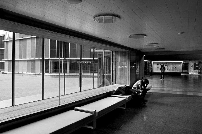 Vista sobre o hall de entrada. Um banco corrido à esquerda com pessoas sentadas  e mais algumas ao fundo no meio da sala