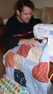 photo of me in my Tommy Hilfiger jumper, sat side-on at the sewing machine with my quilting in progress.