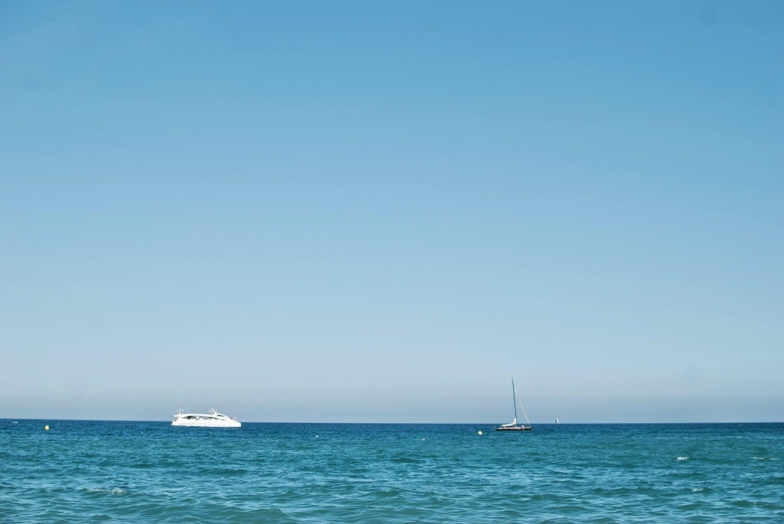 kék ég és kék tenger, rajta két hajó pihen a messzi távolban