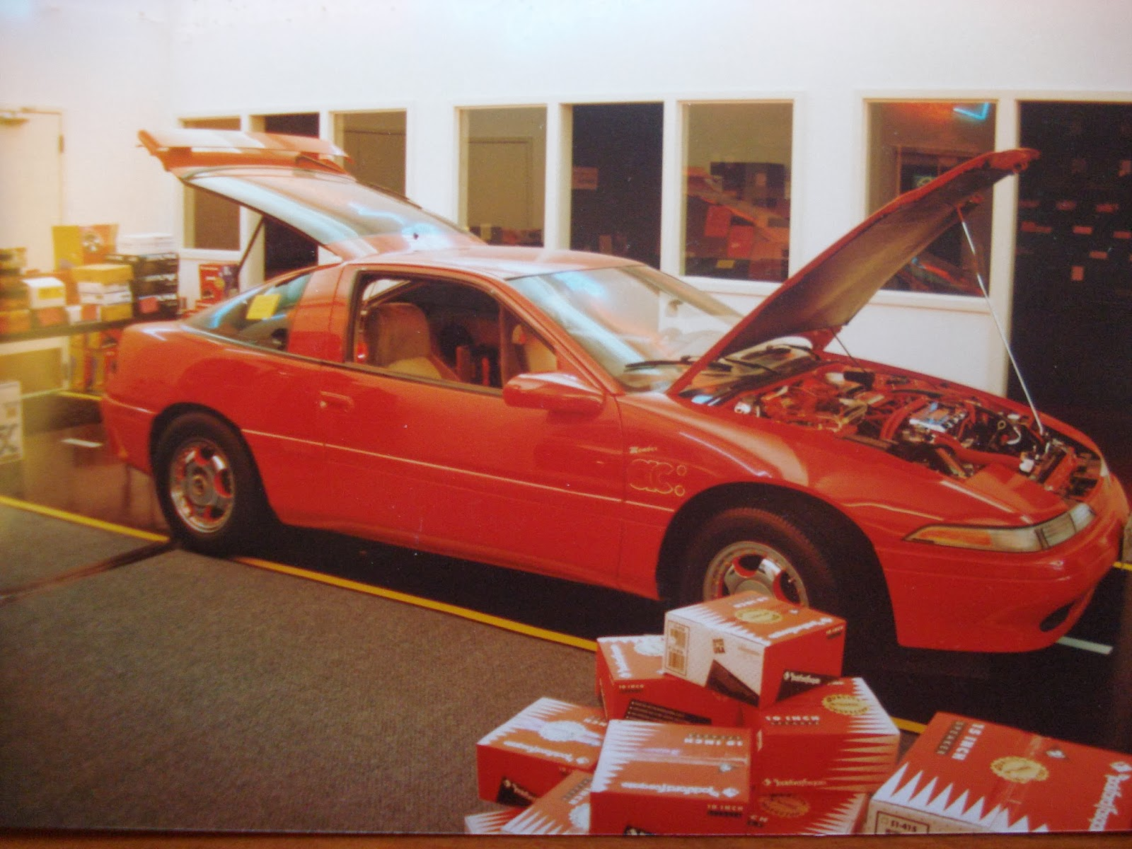 Photo image of the outside of the car (with the hood opened) of Chuck Barbosa's Red Laser as it stood during the winter storage at the end of 1995 and beginning of 1996.