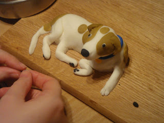 Fondant dog sculpture with details being added